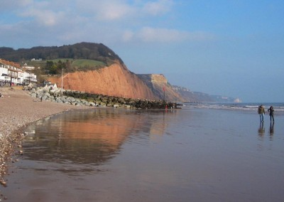 Red cliffs reflected in wet sand as the tide goes out