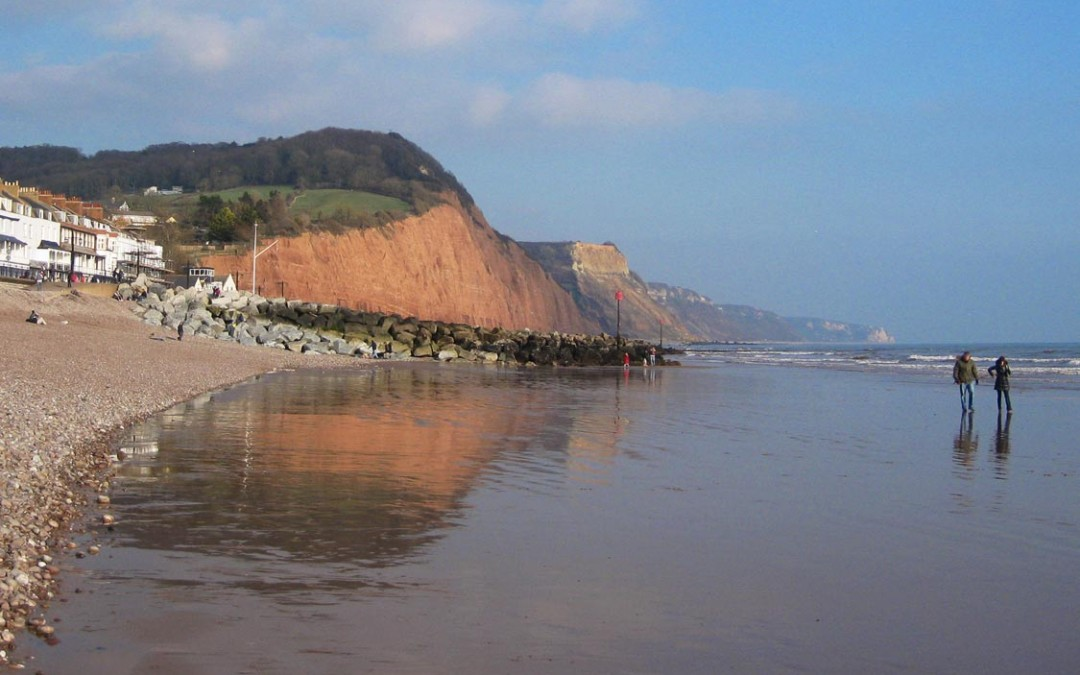 Photo: Red cliffs reflected in wet sand as the tide goes out